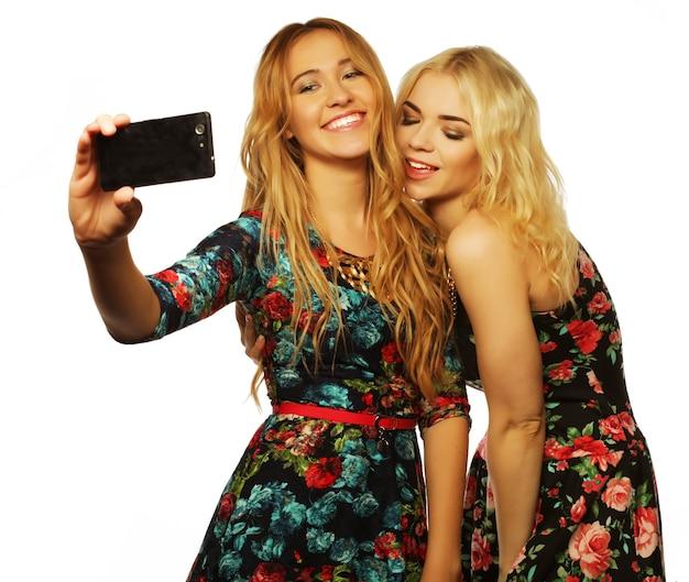 Mujeres jóvenes tomando selfie con teléfono móvil