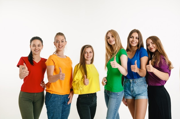 Las mujeres jóvenes vestían los colores de la bandera lgbt aislados en la pared blanca. modelos femeninos con camisas brillantes.