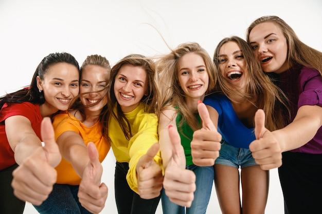 Las mujeres jóvenes vestían los colores de la bandera lgbt aislados en la pared blanca. modelos femeninos caucásicos en camisas brillantes.