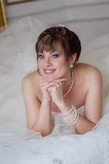 Mujeres jóvenes con vestido de novia en habitación muy luminosa