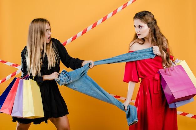 Mujeres jóvenes vistiendo vestidos peleando por un par de jeans con bolsas de compras aisladas sobre amarillo