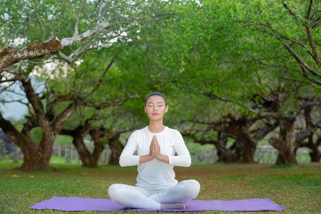 Las mujeres juegan yoga en el parque.