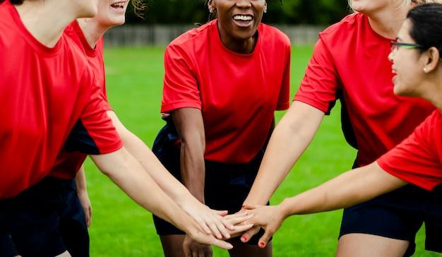 Mujeres jugadoras de rugby apilando sus manos juntas