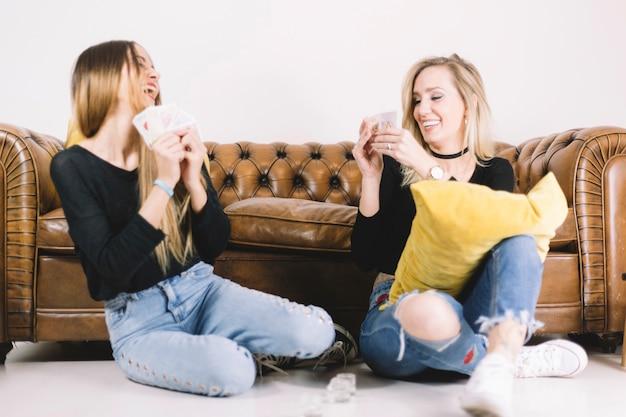 Mujeres jugando a las cartas en el piso Foto gratis