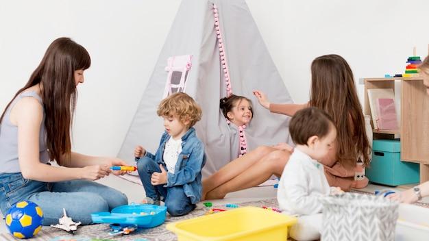 Mujeres jugando en casa con niños y juguetes.