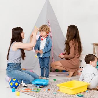 Mujeres jugando con niños en casa