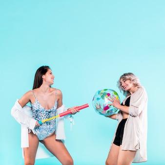 Mujeres jugando con pelota de playa y bomba.