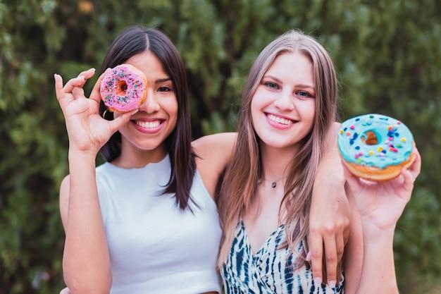 Mujeres juguetonas divirtiéndose con dulces donas