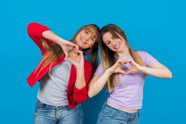 Mujeres juguetonas con las manos en forma de corazón