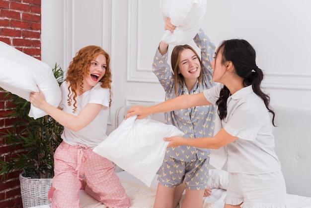Mujeres juguetonas peleando con almohadas