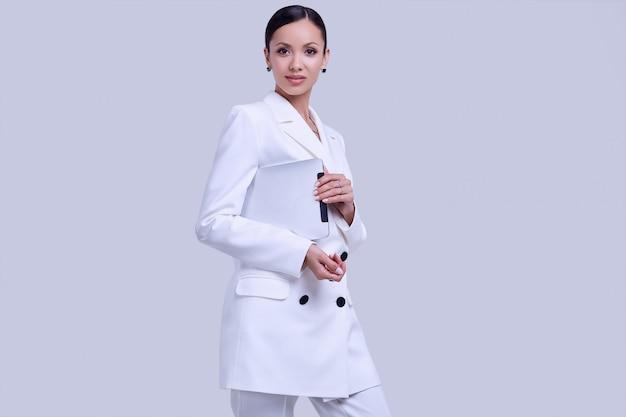 Mujeres latinas hermosas en traje blanco de moda con tableta digital