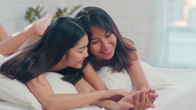 Las mujeres lesbianas asiáticas lgbtq juntan beso y se abrazan en cama en casa.