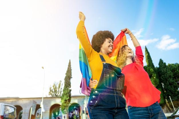 Mujeres lesbianas de diferentes etnias y nacionalidades con bandera gay