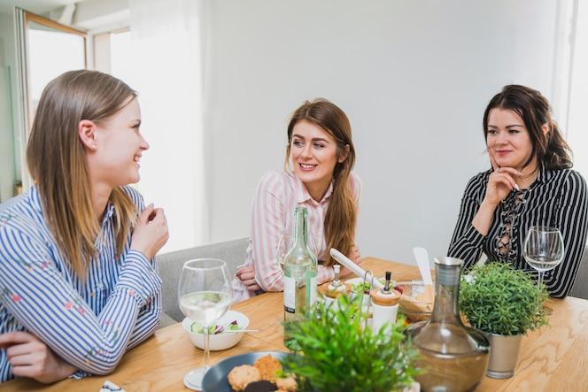 Mujeres lindas en mesa charlando y sonriendo