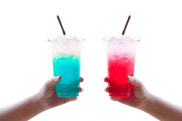 Las mujeres manejan la celebración de agua helada soda italiana rojo y azul en un vaso de plástico, aislado en blanco
