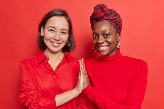 Las mujeres mantienen las palmas juntas muestran apoyo mutuo y comprensión del trabajo mientras el equipo sonríe agradablemente parados hombro con hombro en rojo