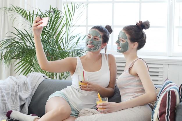 Mujeres con máscara facial tomando un concepto de selfie, belleza y cuidado de la piel