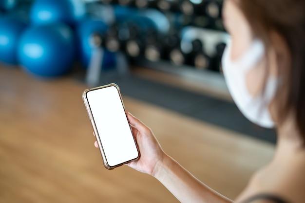 Mujeres con máscara haciendo sosteniendo un teléfono móvil de maqueta en el gimnasio.