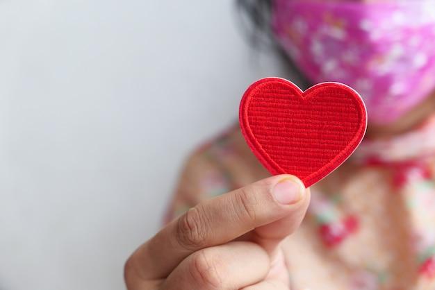 Mujeres en mascarilla protectora con corazón rojo con espacio de copia