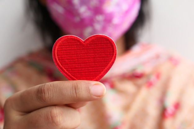 Mujeres en mascarilla protectora con corazón rojo