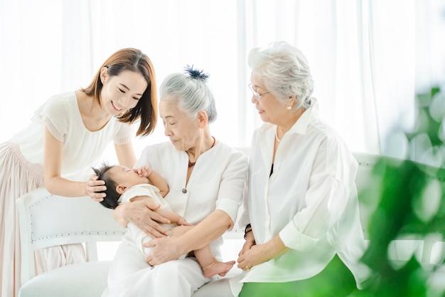 Mujeres mayores abrazando a bebés y mujeres velando
