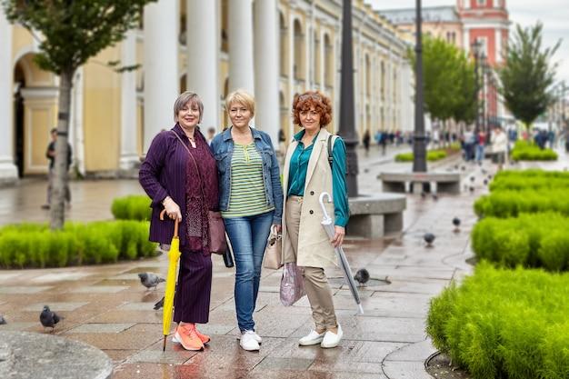 Las mujeres mayores activas se paran en la calle de la ciudad europea en tiempo lluvioso y miran a la lente de la cámara.