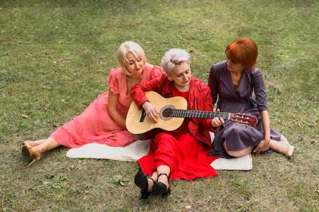Mujeres mayores del ángulo alto que juegan música