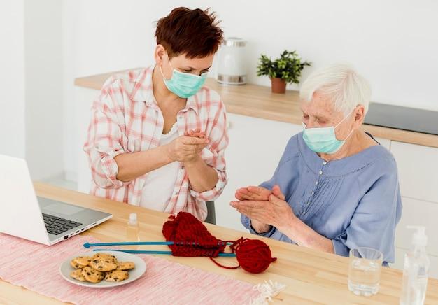 Mujeres mayores desinfectando sus manos en casa