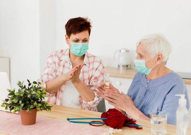 Mujeres mayores desinfectando sus manos mientras están en casa