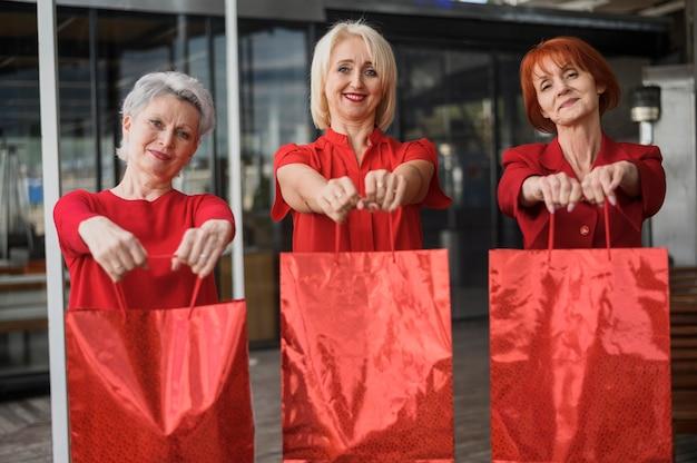 Mujeres mayores felices que sostienen bolsos de compras