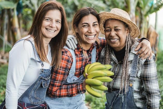 Mujeres mayores multirraciales que trabajan en el jardín mientras sostienen un racimo de plátanos: enfoque principal en el rostro de la mujer del centro