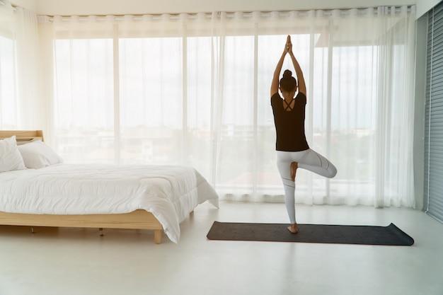 Mujeres de mediana edad haciendo yoga en el dormitorio por la mañana,