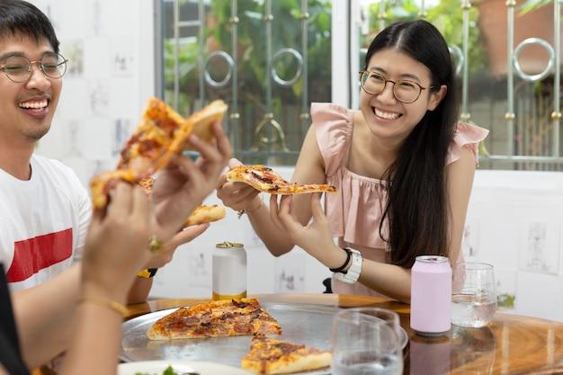 Mujeres con mejores amigos comiendo pizza en el restaurante.