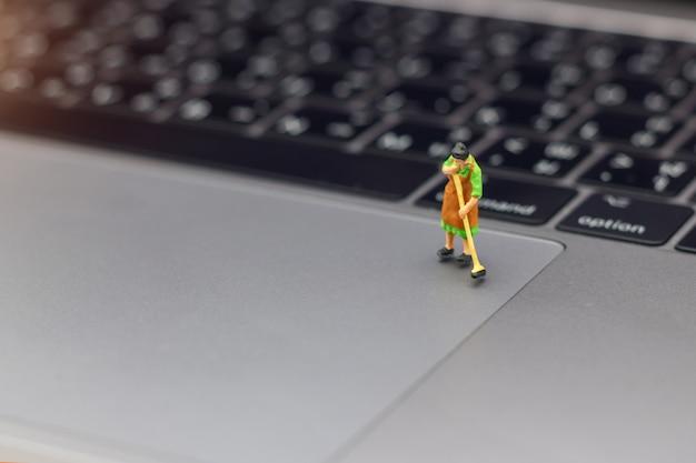 Mujeres miniatura que limpian el ordenador portátil del dispositivo señalador.