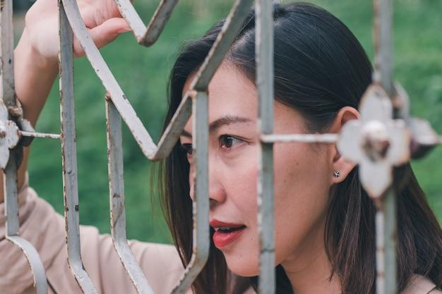 Las mujeres miran hacia afuera y de pie sosteniendo una malla de acero