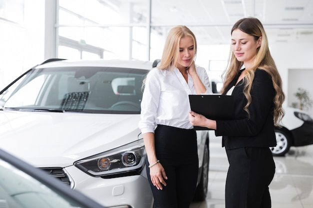 Mujeres mirando portapapeles en concesionario de automóviles