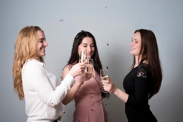 Mujeres de moda alegres tintinean copas de champagne