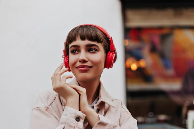 Mujeres de moda en chaqueta de mezclilla beige y auriculares derechos sonriendo afuera