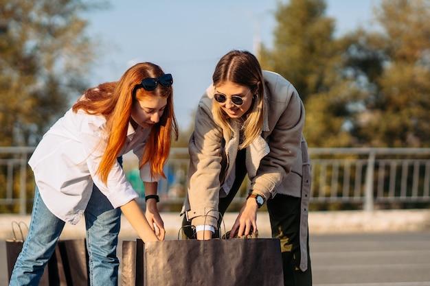 Mujeres de moda joven con bolsas de la compra en el estacionamiento
