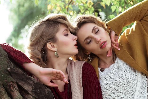 Mujeres de moda posando juntos al aire libre