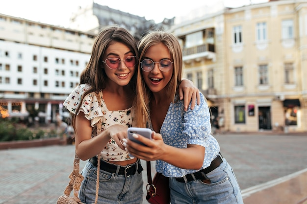 Las mujeres morenas y rubias con trajes elegantes se ven sorprendidas y leen el mensaje en el teléfono celular