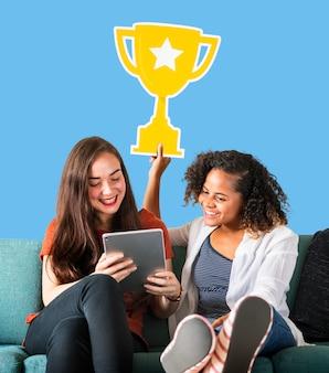 Mujeres mostrando un icono de trofeo y usando una tableta.