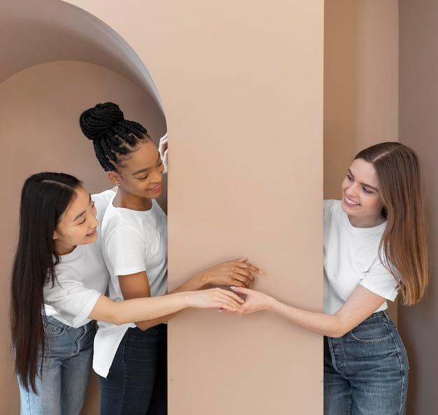 Mujeres multiculturales sonrientes junto a la pared