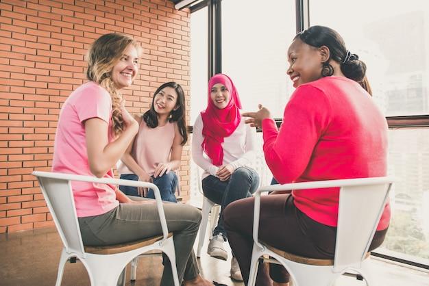 Mujeres multietínicas casuales sentadas en círculo en la reunión.