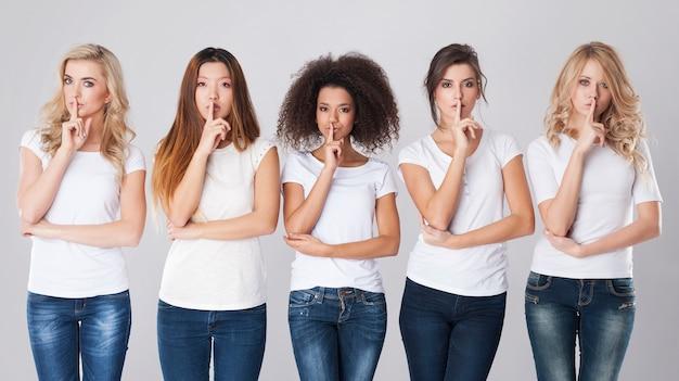 Mujeres multiétnicas con signo de silencio