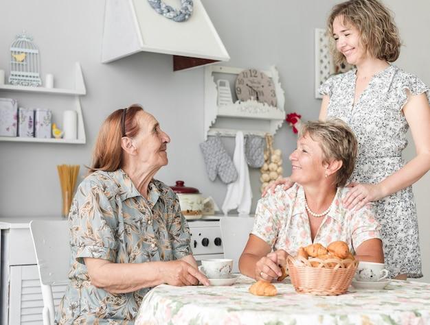 Mujeres multigeneración desayunando en la cocina.