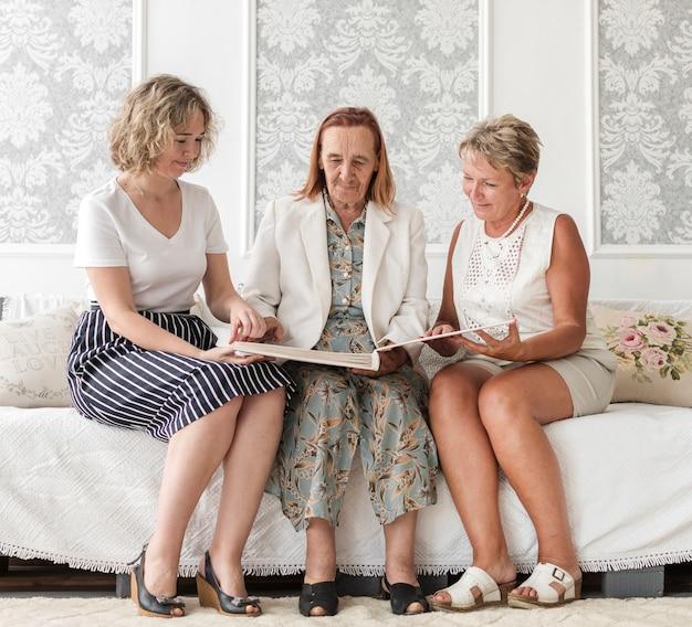 Mujeres multigeneración sentadas en el sofá y buscando un viejo álbum de recuerdos.