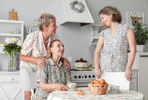 Mujeres multigenerativas hablando entre ellas durante el desayuno.
