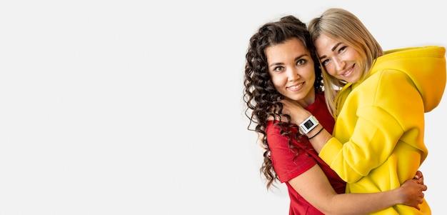 Mujeres multirraciales abrazando con espacio de copia