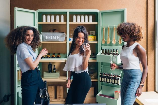Mujeres multirraciales celebrando y bailando en un moderno pub.